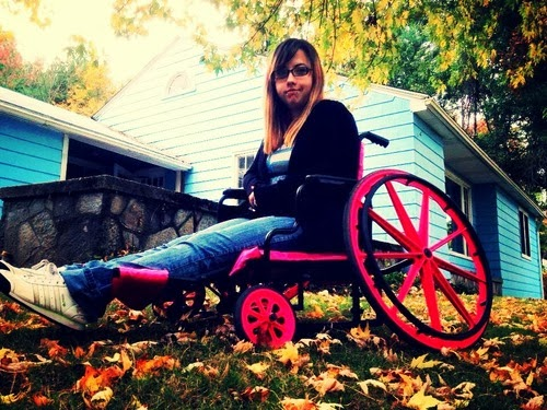 "Young woman in a manual wheelchair that has been modified to ""ride low"", and with pink painted highlights"