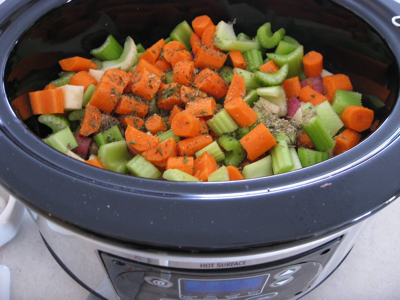 First, chop up all of your veggies and throw them in the slow cooker ...