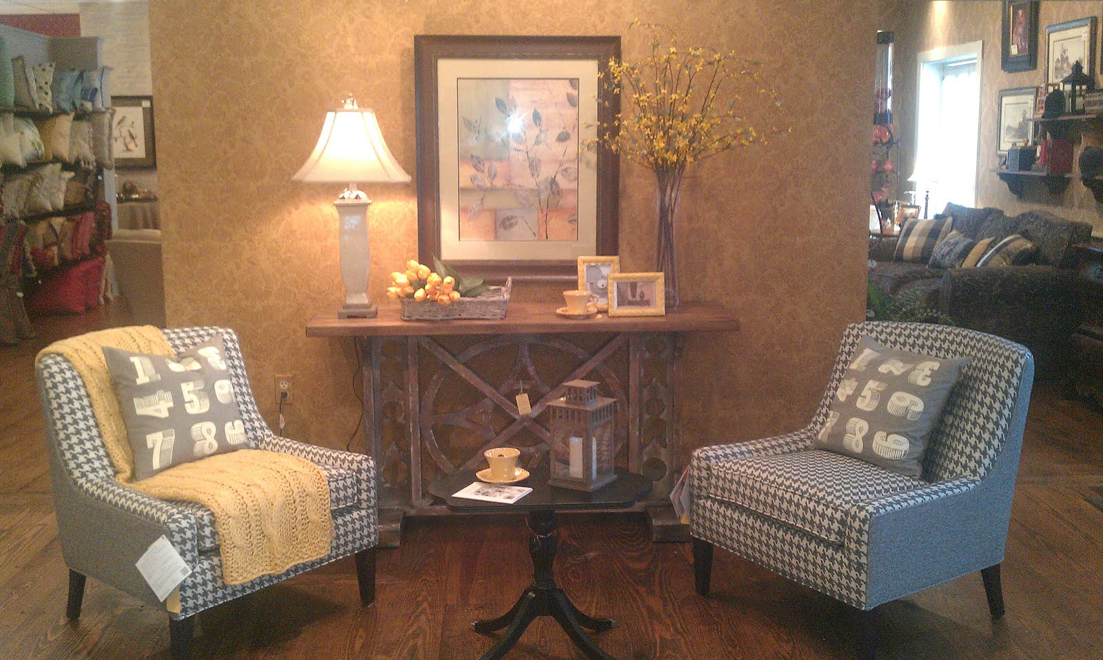 Facing two gray and white houndstooth chairs accented with a yellow