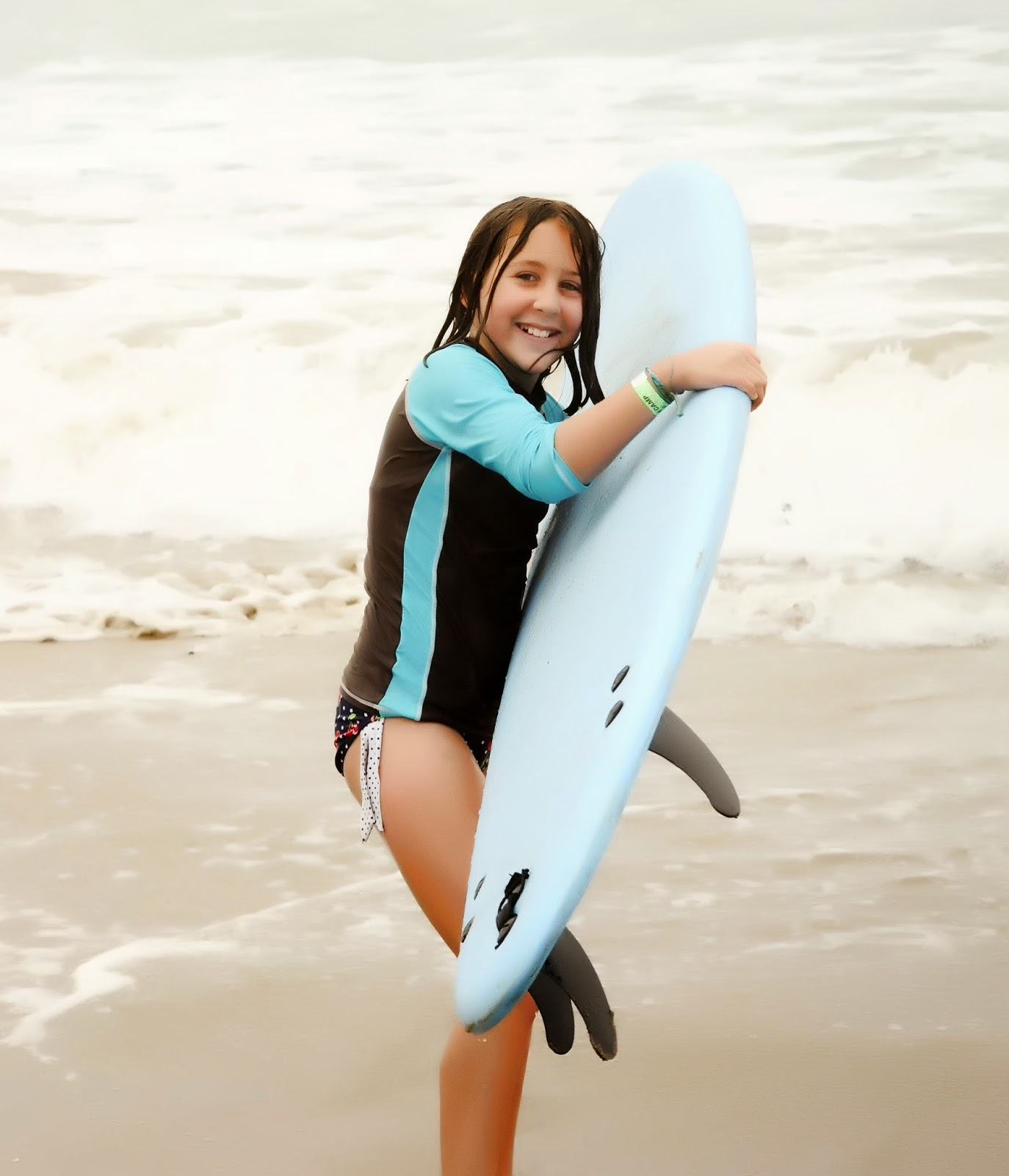 Female camper carrying a surfboard on the beach at Aloha Beach Camp Summer Camp in Los Angeles