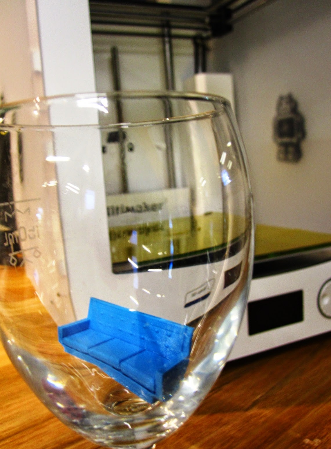 Miniature 3D-printed sofa in an empty wine glass in front of the 3D printer that printed it.