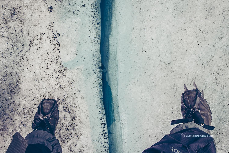 Schuhe mit Steigeisen über Gletscherspalte