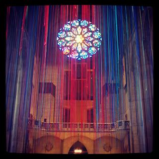 Thousands of different-coloured lengths of ribbon, hanging from the ceiling, facing the West rose window