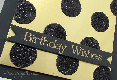 Close-up of gold embossed greeting and glitter spots
