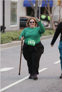 Me with my renaissance walking stick, wearing a green shirt, black pants, race number 1673. I'm giving the photographer a piece sign with my fingers