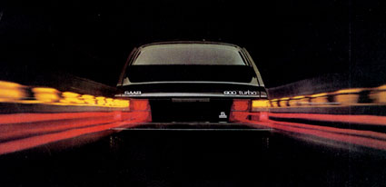 SAAB 900 Turbo with lights on zooming away.