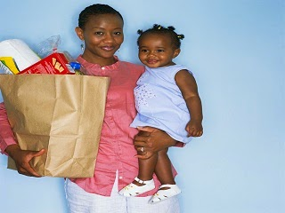 A mother carrying a child on one hand and shopping bag another hand.