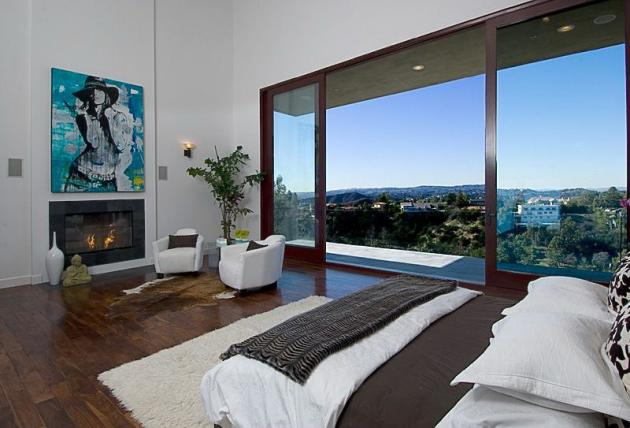Picture of another modern bedroom in the Rihanna's house with fireplace and the balcony
