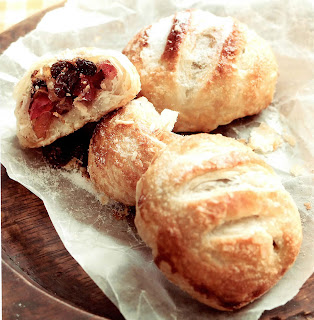 Luxury eccles cakes. Three pastries of mixed dried fruit in a puff pastry shell, one broken open