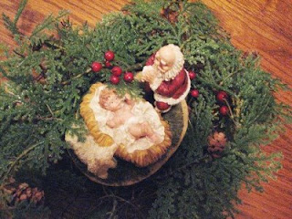 Christmas tree decoration with child Jesus manger and Santa kneeling at stable of Christ photo