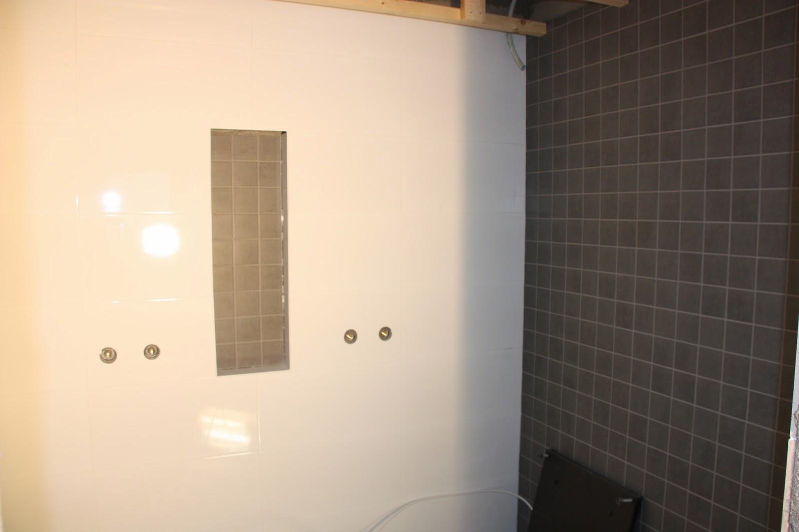 Pukkilan Arc Grafite 10x10 ja valkoinen 30x60-laatta saunan pesutilassa.