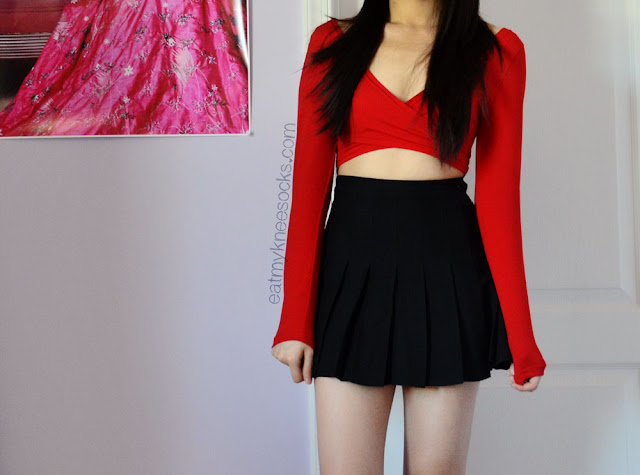 Front view of the red V-neck long sleeve crop top from Milanoo, paired with an American Apparel-style pleated black tennis skirt dupe from SheInside.
