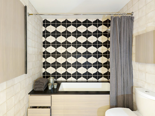 black and white Moroccan tiles in a bathroom with a platform tub by Workstead