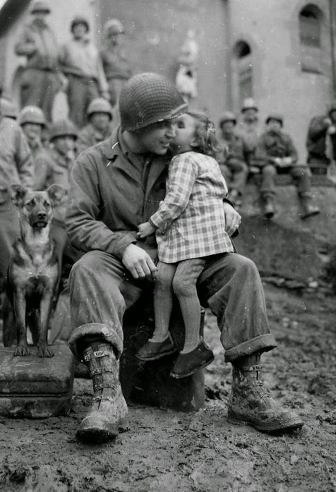 a cute little girl sits on a soldiers lap kissing his cheek