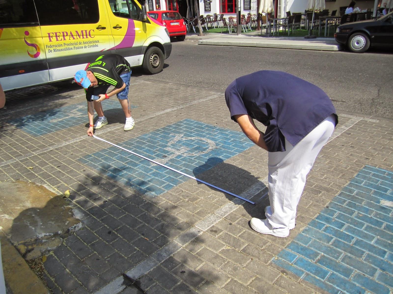 Dos participantes miden el ancho de una de las plazas reservadas.