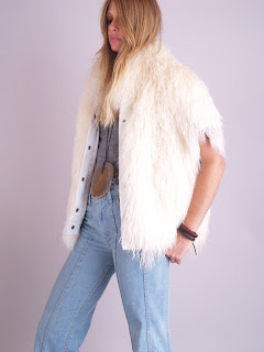 Vintage 1970's fluffy white Mongolian lamb fur vest with snap front closure and pockets.