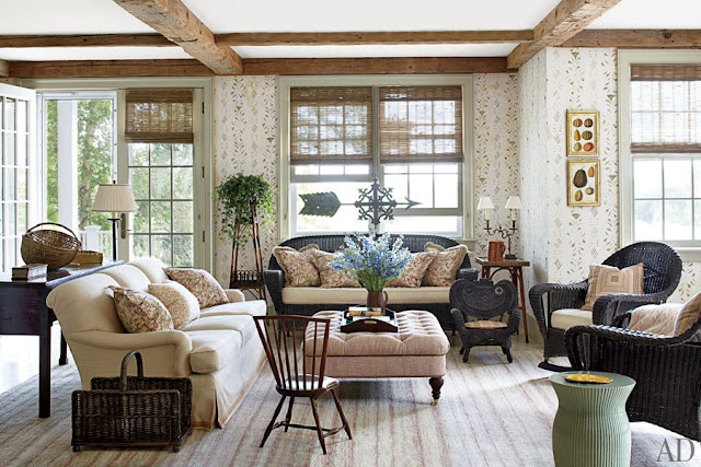 Living room in Nantucket with exposed beams, wood floors, floor to ceiling wall paper, french doors, wicker sofa and matching armchair with an upholstered sofa and an ottoman being used as a table.