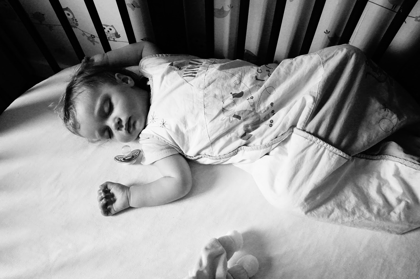 Black and white baby sleeping in cot