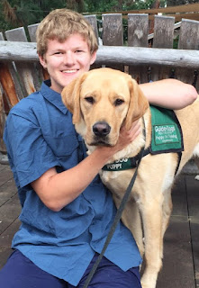 Sam smiles with a yellow Lab guide dog puppy.