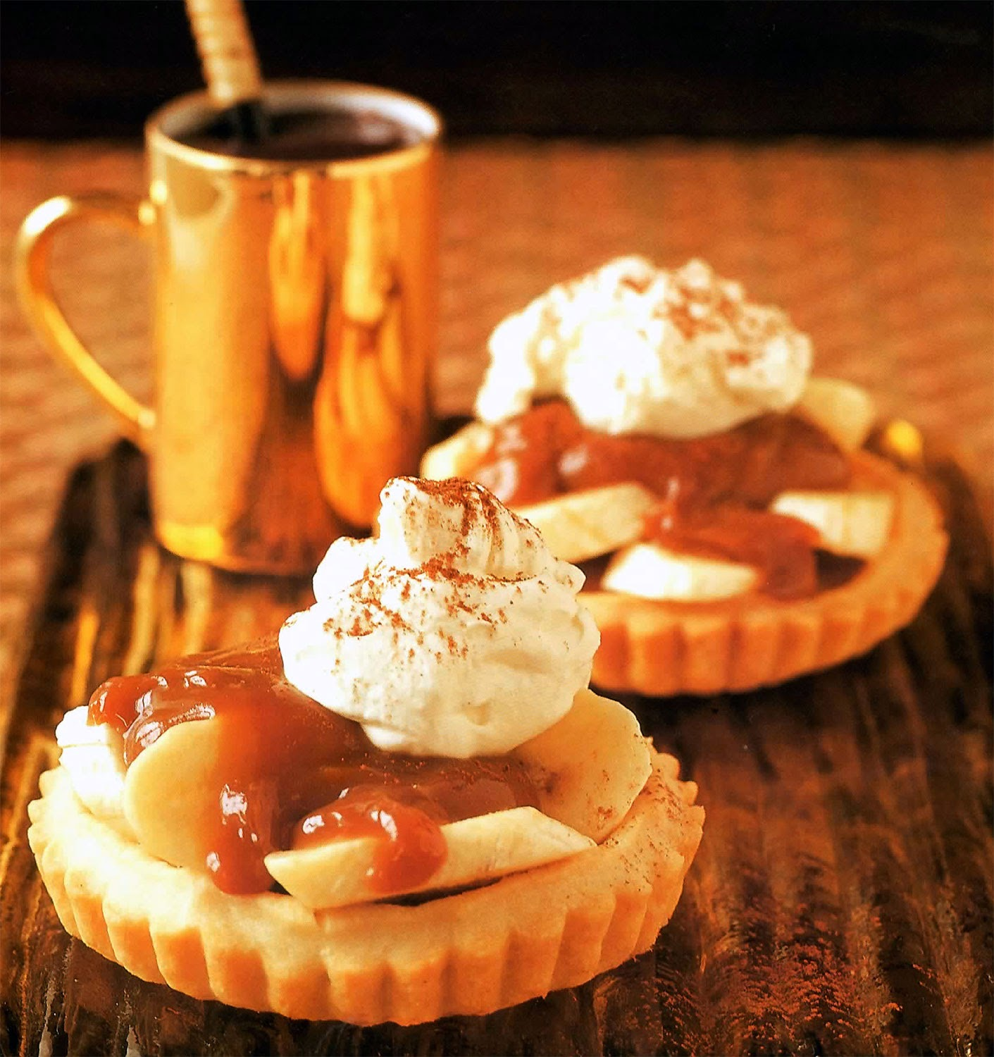 Banoffee Tarts Recipe: Miniature banoffee pies in a baked shortcrust shell, topped with whipped cream and fudge sauce