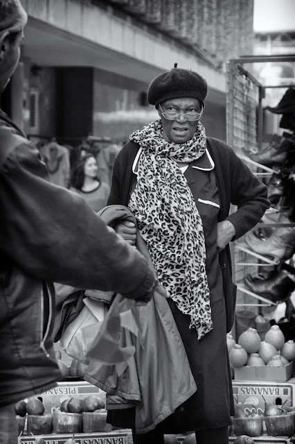A woman negotiates the price of fruit with a street vendor on Cape Town's St George's Mall