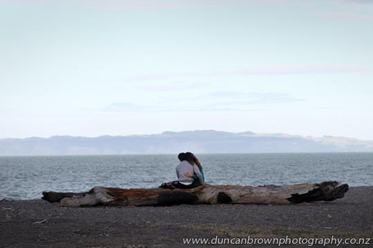 Young love, couple on a log, Pacific Beach, Marine Parade, Napier photograph