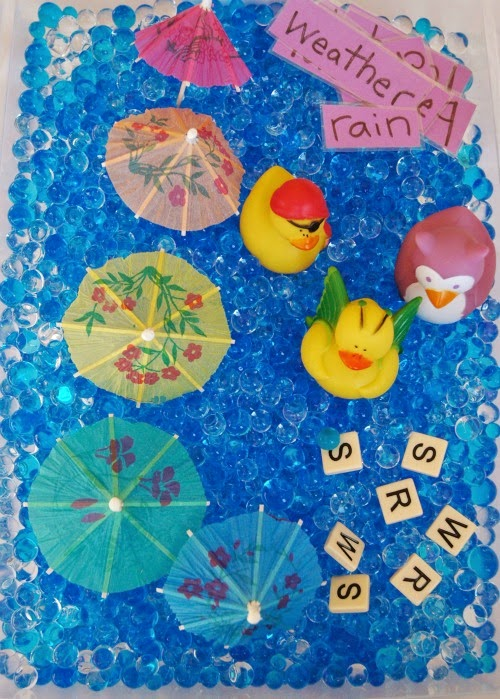rainy day sensory bin with rubber ducks, paper umbrellas, water beads