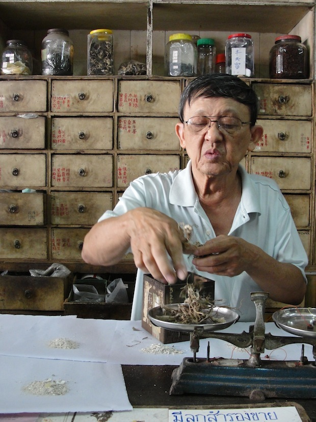 traditional chinese herbalist in old phuket town, measuring herbs