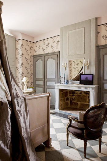 bedroom in a french mansion with pink and grey wallpaper, a painted checkered wood floor, a white fireplace, paneled doors and a Louis XIV chair