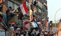 Protesters celebrating as they demolish a wall at the Israeli embassy in Cairo.