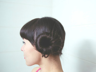 young woman with dark hair in side buns, in profile