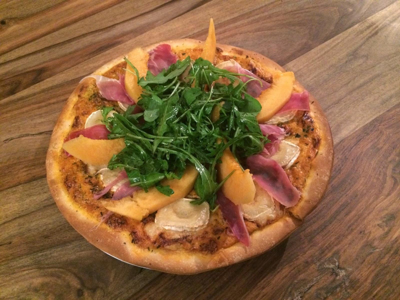 Pizza blanche au jambon cru, fromage de chèvre, roquette et melon
