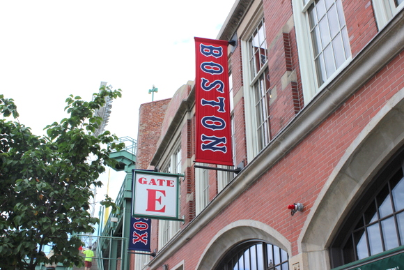 This Red Sox stadium in Boston has red brick along with red and blue signs.