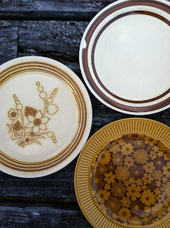A shot of three old china plates on a picnic table.