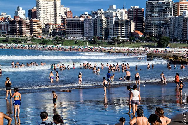 Playa con gente en el agua y la Ciudad de Mar del Plata al fondo.