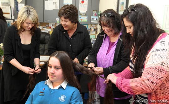 Standing L-R: Rachel Palmer, hairdresser, Head High Hair Design, Hastings, Colleen Birch, aunt, Lisa Greaney, mother, Laura Birch, cousin, plaiting twelve year-old Lucy Belle Greaney's metre-long hair, before it was cut off from shoulder-length, to be made into wigs. Lucy also raised $1,063 for Child Cancer at St Patrick's School in Napier. photograph