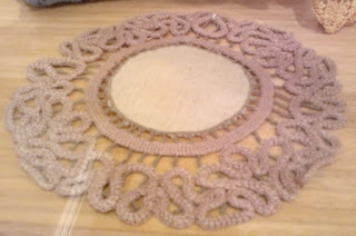 Table mat with a cloth centre and needleworked border. The border is made of serpentine shapes, and attached to the centre by fine beaded threads.