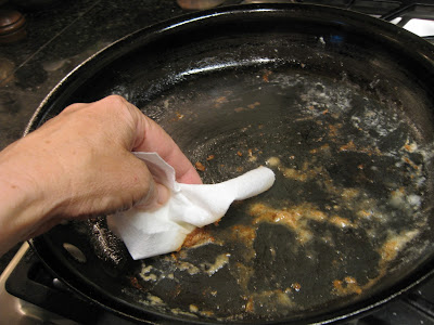 hand with paper towel wiping dirty pan clean