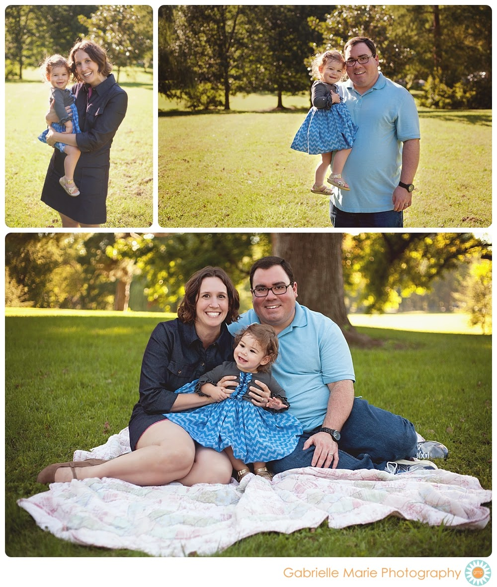 Family in blue with 18 month girl sitting on a quilt in a park.