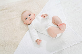 Picture shows swaddle opend out in diamond shape and folded into a triangle with baby placed on top.