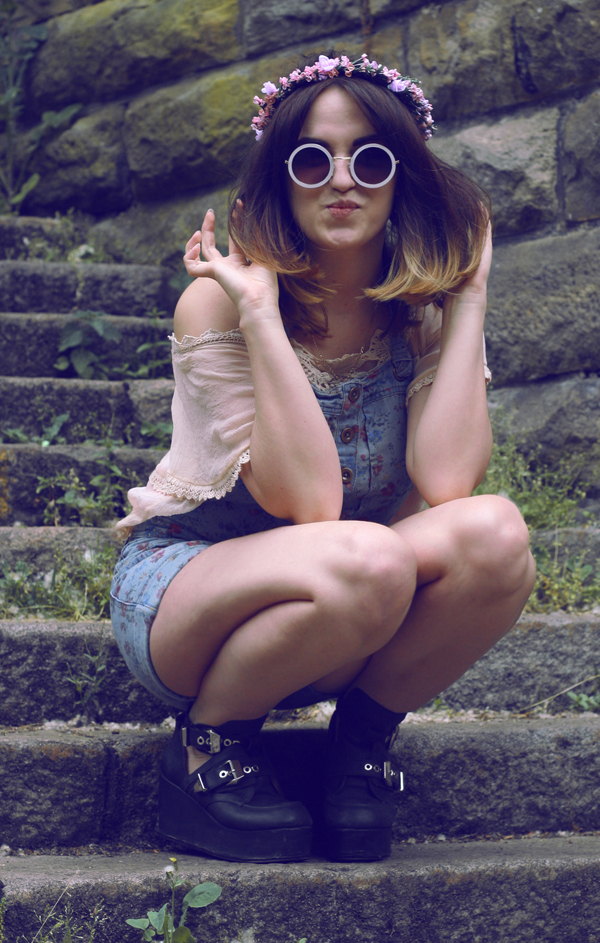 hippy girl, vintage 70s circle sunglasses, wild flower garlands, vintage darling camisole, floral overalls, jeffrey campbell platform boots. sitting down