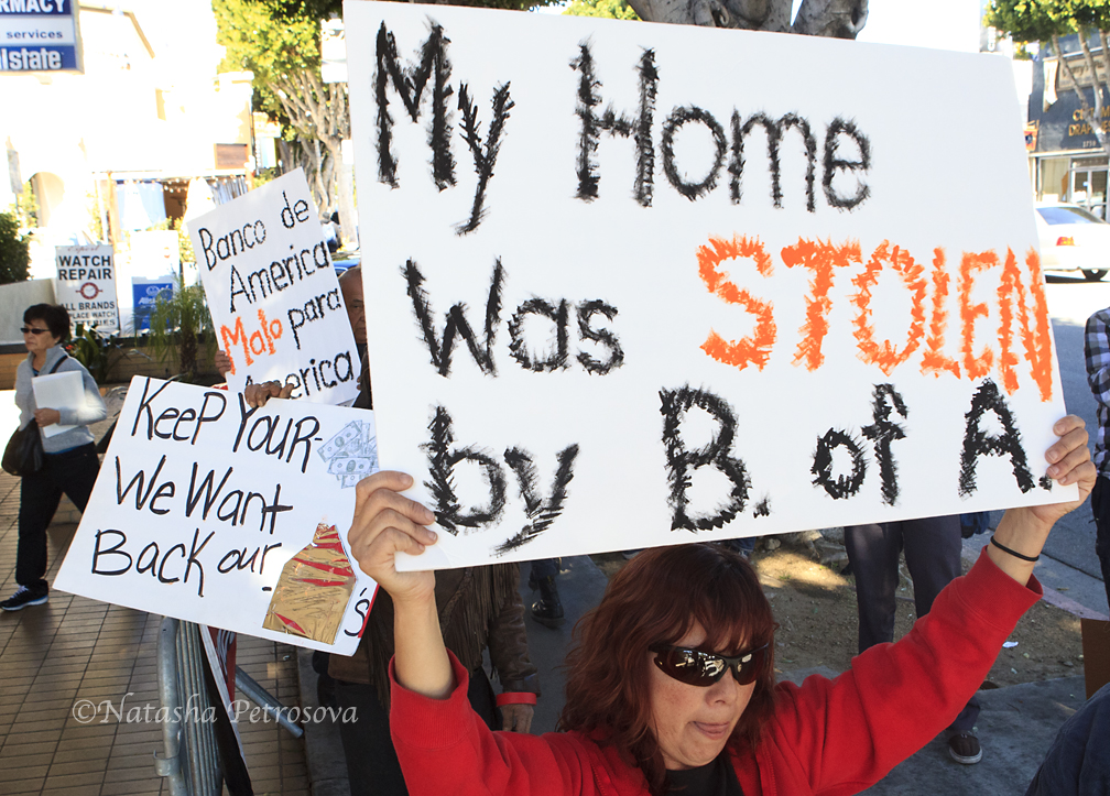 Soledad Corona, a recent victim of fraudulent foreclosure holds the sign.