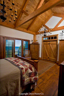 This lakeside timber frame bedroom features soaring ceilings and a balcony
