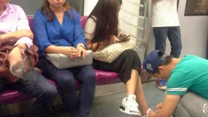 Foto Menyedihkan: Pria Pasang Tali Sepatu Pacarnya di Kereta Api