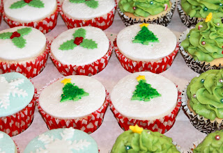Set of Christmas cupcakes, including holly-topped, Christmas tree topped and snowflake topped cupcakes