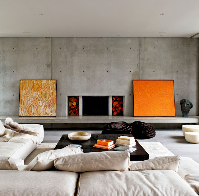 Modern living room with concrete wall and orange paintings