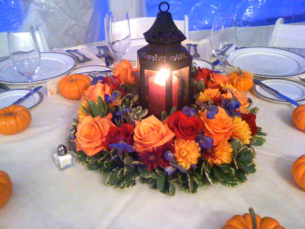This fall lantern centerpiece cleverly incorporates roses mums and