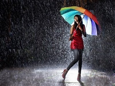 Feliz apesar da chuva com guarda-chuva colorido