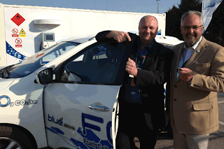 Dr Graham Cooley, CEO of ITM Power, David Green, CEO of Eco-island, celebrating their win alongside a Hyundai electric fuel cell vehicle