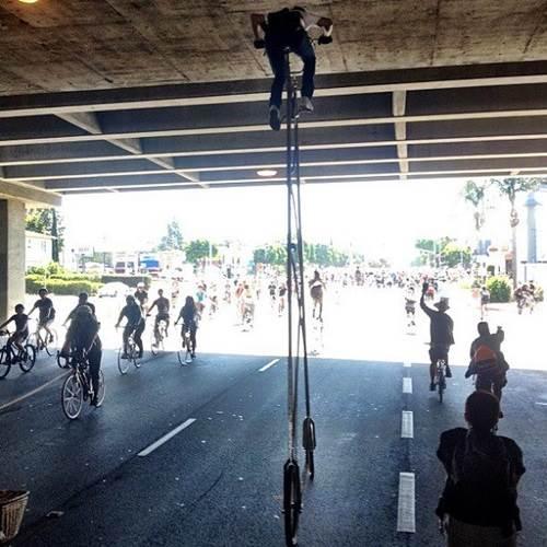 menunggang basikal tinggi di bawah jambatan